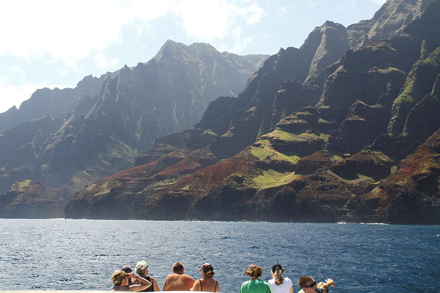 A group views the Na Pali Coast scenery from the front of our boat